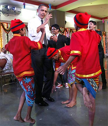 US President Barack Obama dances with children during his visit to the Holy Name High School in Mumbai