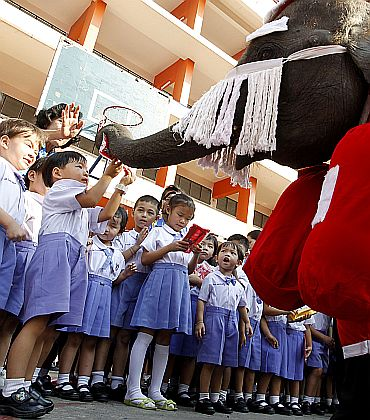 An elephant dressed as Santa Claus distributes candy to students during Christmas celebrations at Jirasart school in Ayutthaya, 70 km (44 miles) north of Bangkok, Thailand