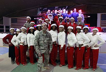 An American military personnel pose with performers from the United States following a Christmas Eve concert at Bagram Airfield, north of Kabul, Afghanistan