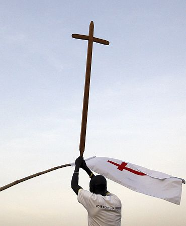 A Sudanese man wearing a t-shirt reading, 'Vote For Your Freedom' holds up a cross during a Christmas Eve procession in Juba