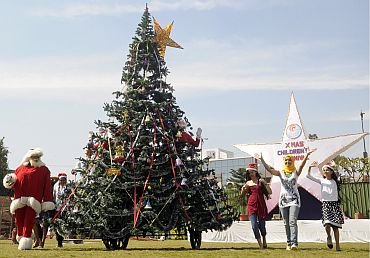 A woman wearing a Santa Claus dress looks at a Christmas tree shaped tricycle as part of Christmas celebration in Hyderabad