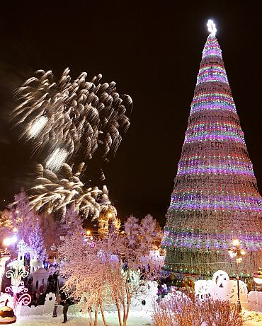 Fireworks explode around a Christmas tree during festivities in the centre of the Siberian city of Krasnoyarsk