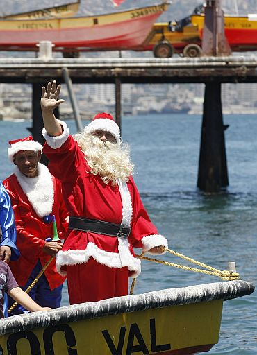 Ruben Torres, dressed in a Santa Claus outfit, and fishermen wave to people from a boat on Christmas Eve along the coast of Valparaiso city, about 75 miles (121 km) northwest of Santiago, the Chilean capital. Every year, fishermen in Valparaiso organise a Santa Claus boat trip as people wait on the shore to receive their Christmas presents and well-wishes