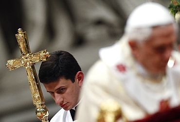 An altar boy holds Pope Benedict XVI's pastoral cross as he leads the Christmas mass in Saint Peter's Basilica at the Vatican