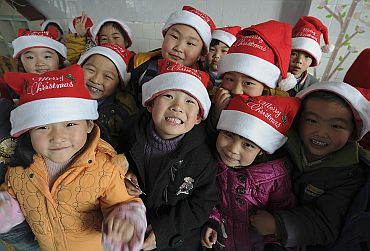 Children wearing Santa Claus hats pose for a photograph as they celebrate the Christmas Day at a kindergarten at Hefei, Anhui province of China