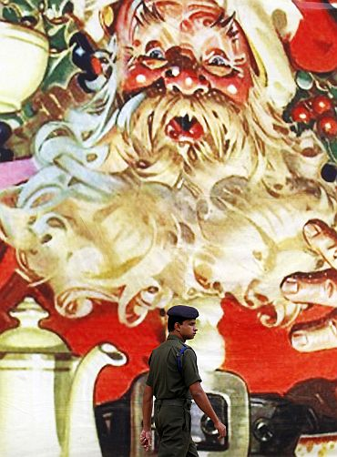 A Sri Lankan army soldier walks past a Santa Claus banner in Colombo on Christmas Eve