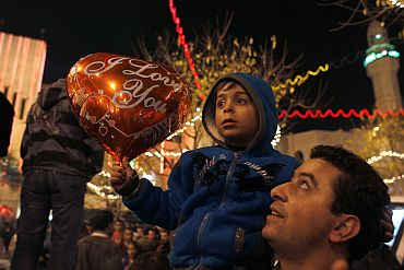 A Palestinian boy sits on his father's shoulder at Manger Square outside the Church of the Nativity, the site revered as the birthplace of Jesus, in the West Bank town of Bethlehem on Christmas Eve