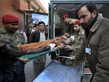Paramedics and soldiers assist a man who was injured during a suicide bomb attack in Bajaur region,