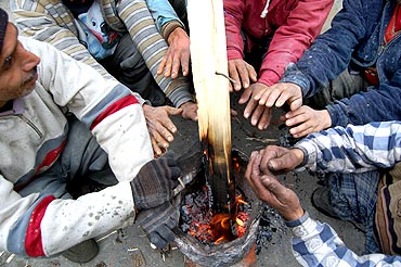 Locals warm themselves as freezing cold grips Kashmir