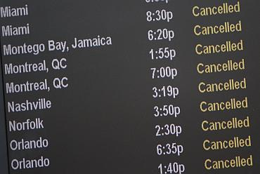 A board lists cancelled flights at JFK International Airport in New York