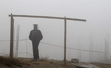 A security staff stands guard at a construction site amid heavy fog near the airport in New Delhi