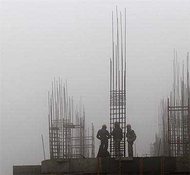 Labourers work at a construction site amid heavy fog near the airport in New Delhi