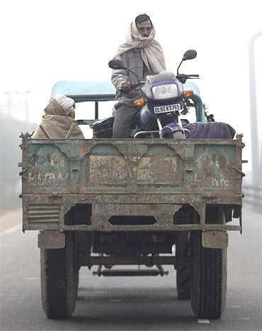 A man sits on his motorcycle on a trailer attached to a tractor on a foggy morning in New Delhi