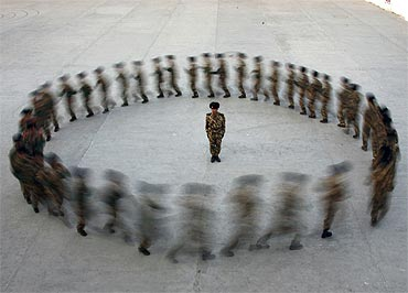 A commander watches as recruits of paramilitary police run in a circle during a training at a military base in Hami, Xinjiang