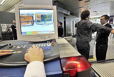 Security personnel check a passenger and his bags through an X-ray machine