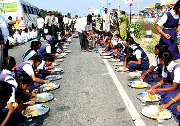 Schoolchildren partake in mid-road feast