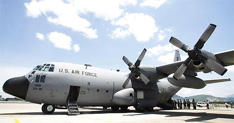 U.S. military personnel stand near a C130 aircraft