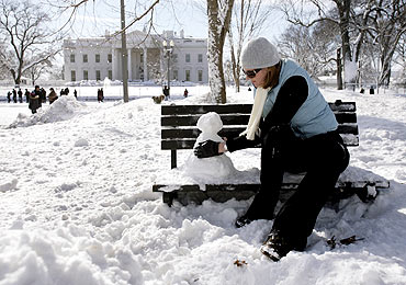 Emily Eelman makes a snowman in front of the White House in Washington