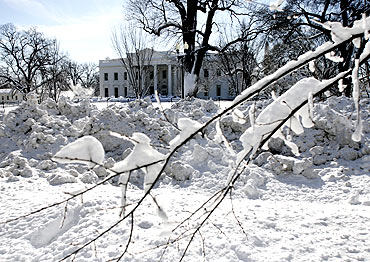 Plowed snow is seen along Pennsylvania Avenue, with the snow-covered White House in the background
