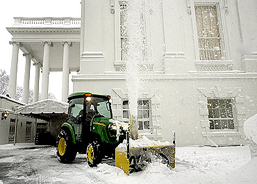 A snow blower clears snow from a driveway around the White House