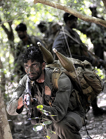 A file photo shows Sri Lankan soldier keeps watch during a patrol in the jungle in the Puthukkudiyirippu area