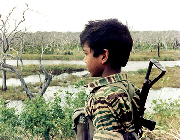 An undated picture supplied by the Sri Lankan Ministry of Defence from a collection of photographs that government soldiers said were discovered recently in a hideout in northern Sri Lanka, shows a boy dressed in LTTE uniform