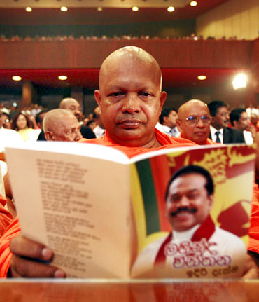 A Buddhist monk reads Sri Lanka President Mahinda Rajapaksa's election manifesto in the run-up to the presidential elections