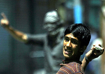 A Kashmiri protester throws a stone at police during a demonstration in Srinagar