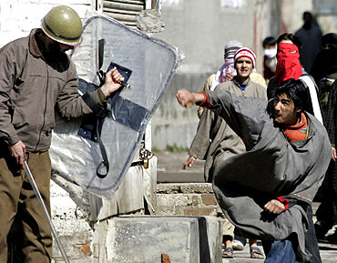 A Kashmiri protester throws a rock towards a state police officer during a protest in Srinagar