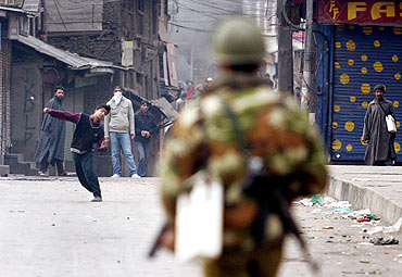 A Kashmiri protester throws a stone towards a policeman during a strike