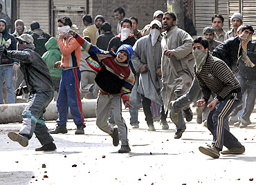 Kashmiri demonstrators throw stones and pieces of bricks towards policemen during a protest in Srinagar