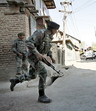 A soldier runs during a gun battle with militants in Sopore