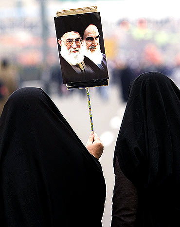 A woman carries a placard with the images of Iran's Supreme Leader Ayatollah Ali Khamenei (L) and founder of the Islamic Republic Ayatollah Ruhollah Khomeini