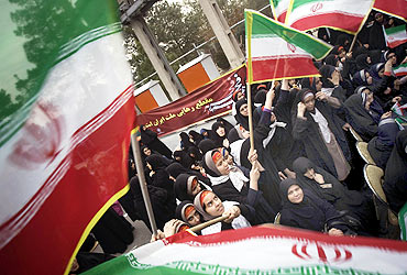 Schoolgirls wave Iran flags during a ceremony to mark the anniversary