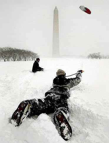 A woman kitesurfs near the Washington Monument during a snow squall on the National Mall in Washington