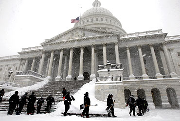 Workers clear snow from the steps of the US Capitol in Washington