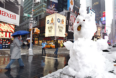 A snowman with a pickle nose and eyes made of pennies sits in Times Square in New York