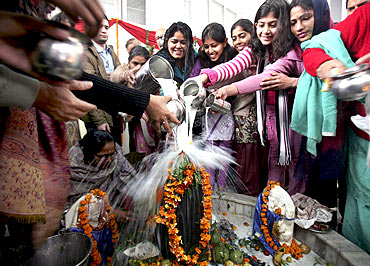 Women pour milk over a Shivling during the Mahashivratri festival in Chandigarh