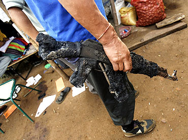 A policeman holds a burnt weapon at a police camp attacked by Maoist rebels