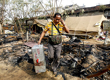 A policeman carries his colleague's belongings at a police camp that was attacked by Maoist rebels