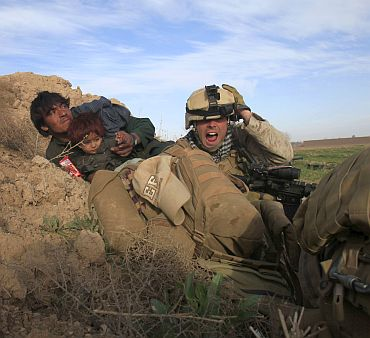 A US Marine from Bravo Company, 1st Battalion, 6th Marines, gestures as he tries to protect an Afghan man and his child after Taliban fighters opened fire in the town of Marjah