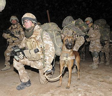 Corporal Lino Woolf keeps a firm grasp of his search dog before being mobilised for Operation Moshtarak