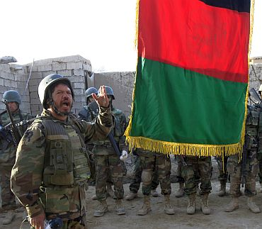 An Afghan soldier speaks during a flag raising ceremony in the town of Marjah