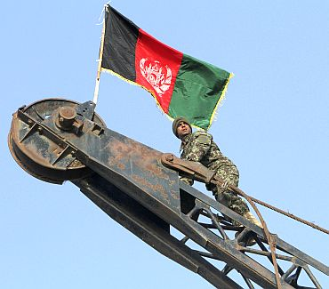 Private Aziz Watandosd, 22, of 2nd Company 1st Battalion, 201st Corp of the Afghan National Army looks on after climbing a crane to raise the Afghan national flag after removing the Taliban's white flag in the former Taliban stronghold of central Showal