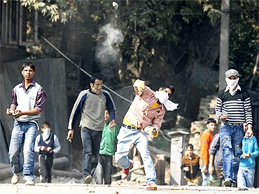 A Kashmiri protester throws a stone towards the police during a protest in Srinagar