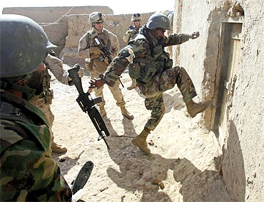 An Afghan soldier attempts to break open a door as US Marines look on during an operation in the town of Marjah in Helmand province