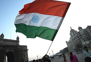 A peace activist waves the national flag in front of the Taj Mahal hotel in Mumbai