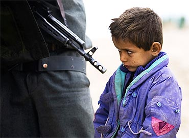 An Afghan boy looks on as his father is searched by a policeman at a checkpoint at Delaram district in Nimroz province, southern Afghanistan