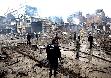 An Afghan policeman stands at the site of a blast in Kabul on Friday