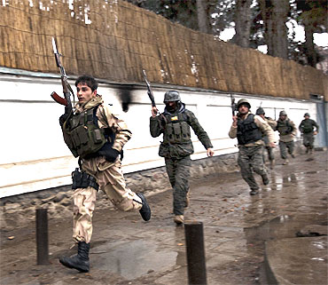 Afghan military personnel rush to the site of a fire fight with the Taliban in Kabul
